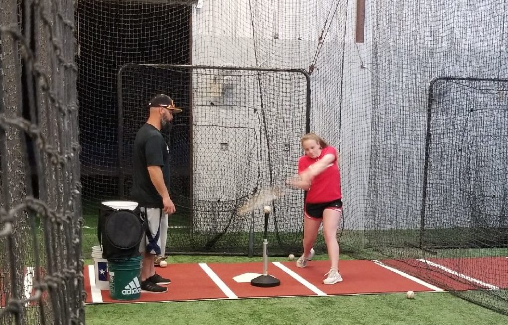 softball lesson with coach in batting cage